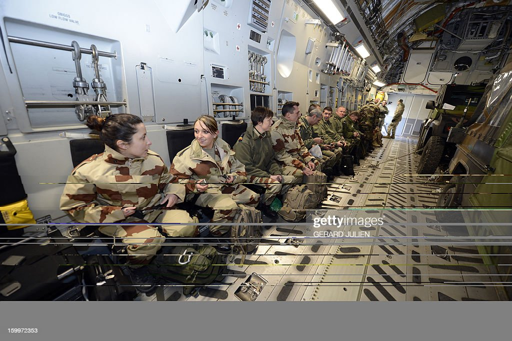 French soldiers sit aboard a C17 aircraft of the US Airforce carriying French armoured vehicles at the Istres military airport (BA 125) on January 24, 2012 in Istres, southern France, prior to take off and heading toward Mali as part of the 'Serval' operation.
