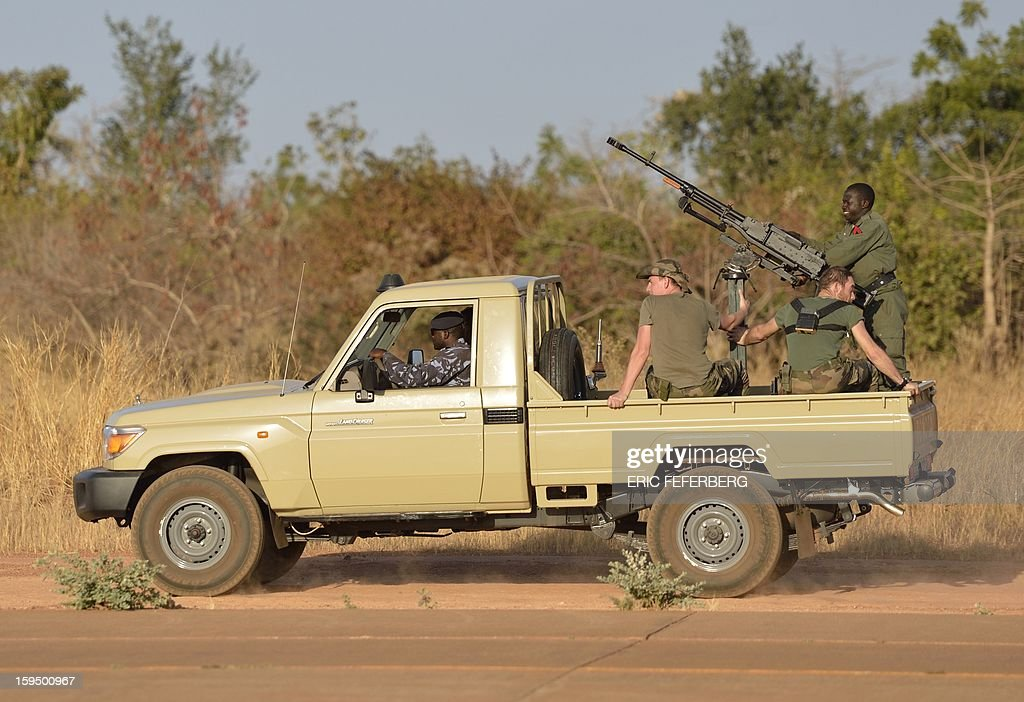 French soldiers sit aboard a Malian military armed car at the 101 military airbase near Bamako on January 14, 2013. France is using air and ground power in a joint offensive with Malian soldiers launched on January 11 against hardline Islamist groups controlling northern Mali.