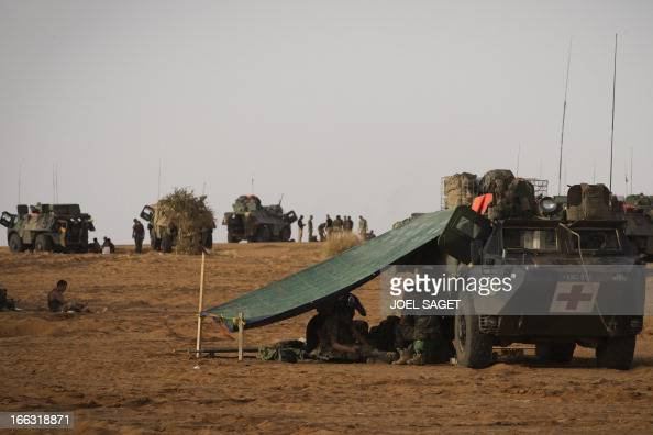 French soldiers sit next to a ambulance armoured vehicle on April 10 105 kms north of the northeastern Malian city of Gao in day three of Operation...