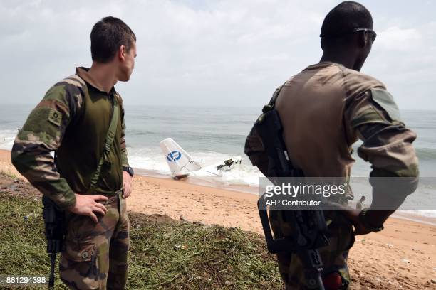 French soldiers stand guard at beach of PortBouet in Abidjan on October 14 2017 as they look at the wreckage of a cargo plane that crashed off Ivory...
