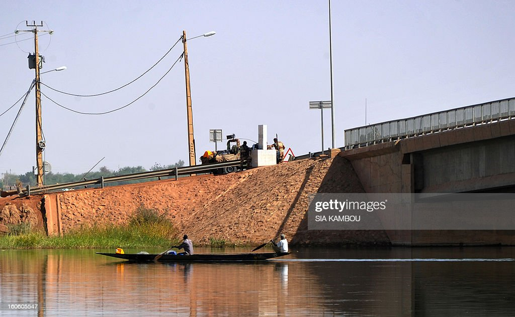 French soldiers stand guard near a bridge on the Niger river as fishers pass by on February 3, 2013 in Gao. France said it carried out major air strikes today near Kidal, the last bastion of armed extremists chased from Mali's desert north in a lightning French-led offensive.