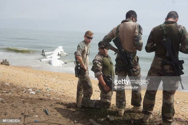 French soldiers stand on the beach of PortBouet in Abidjan near the wreckage of a cargo plane that crashed off Ivory Coast killing four on October 14...