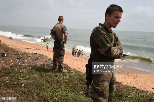 French soldiers stand on the beach of PortBouet in Abidjan on October 14 2017 as rescuers try to pull out the wreckage of a cargo plane that crashed...