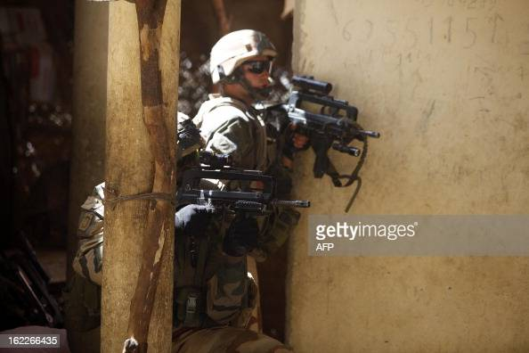 French soldiers stay covered while clashes erupted in the city of Gao on February 21 2013 and an apparent car bomb struck near a camp housing French...