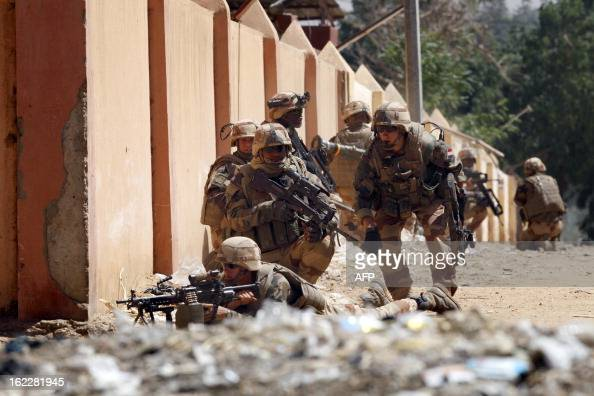 French soldiers take cover as they fight while clashes erupted in the city of Gao on February 21 2013 and an apparent car bomb struck near a camp...