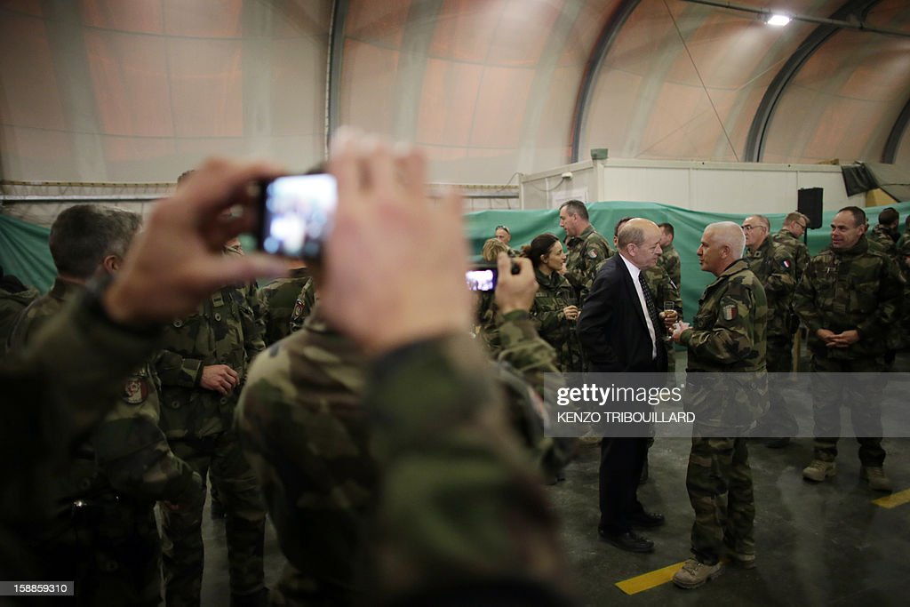 French soldiers takes pictures of French Defence Minister Jean-Yves Le Drian (2ndR) as he speaks with a French soldier during his New Year wishes to French soldiers at Kabul International Airport (KAIA) on January 01, 2013.