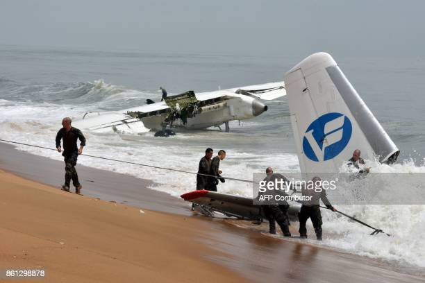 French soldiers try to pull the wreckage of a cargo plane that crashed off Ivory Coast and killed four people from the sea at the beach of PortBouet...
