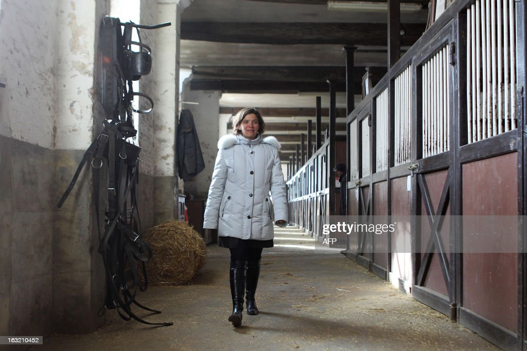 French Sophie Lemaire, the new 'Haras du Pin' director, pets a horse as she poses in the stables, on March 4, 2013 in Le Pin-au-Haras, northwestern France. It is the first time since its creation in 1715 by French King Louis XIV that the world known Haras du Pin is headed by a woman.The