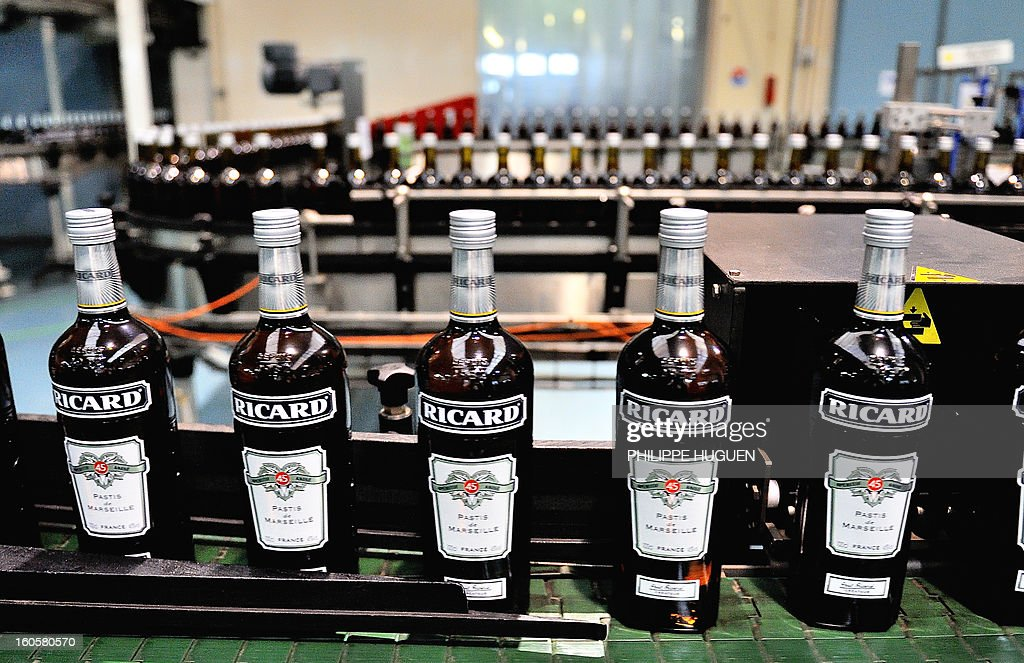French spirit Pernod-Ricard bottles of star aniseed-based spirit Ricard are pictured on the chain of bottling on January 31, 2013 in Vendeville, northern France. The famous star anise spirit Ricard was created in 1932 by French Paul Ricard and became Pernod-Ricard group in 1975.