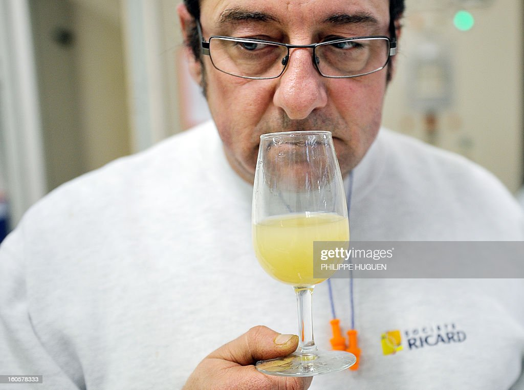 A French spirit Pernod-Ricard employee smells a glass of star aniseed-based spirit Ricard for quality check in the lab on January 31, 2013 in Vendeville, northern France. The famous star anise spirit Ricard was created in 1932 by French Paul Ricard and became Pernod-Ricard group in 1975. AFP PHOTO PHILIPPE HUGUEN