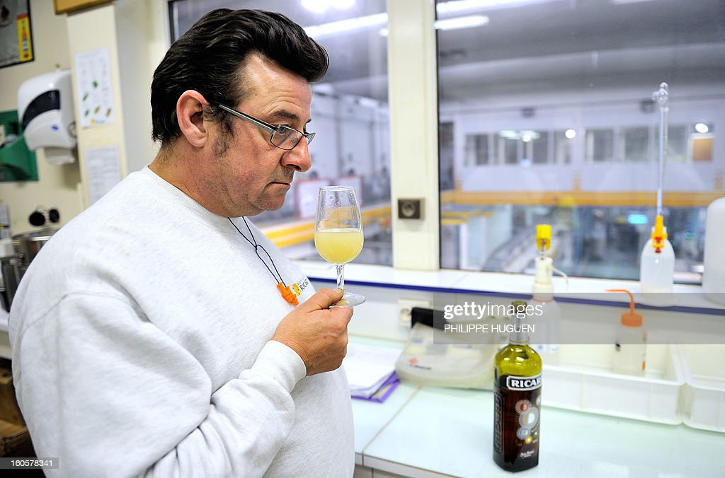 A French spirit Pernod-Ricard employee smells a glass of star aniseed-based spirit Ricard for quality check in the lab on January 31, 2013 in Vendeville, northern France. The famous star anise spirit Ricard was created in 1932 by French Paul Ricard and became Pernod-Ricard group in 1975.