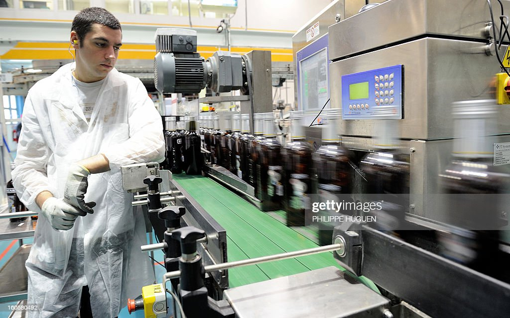 A French spirit Pernod-Ricard employee works on the chain of bottling of star aniseed-based spirit Ricard on January 31, 2013 in Vendeville, northern France. The famous star anise spirit Ricard was created in 1932 by French Paul Ricard and became Pernod-Ricard group in 1975.