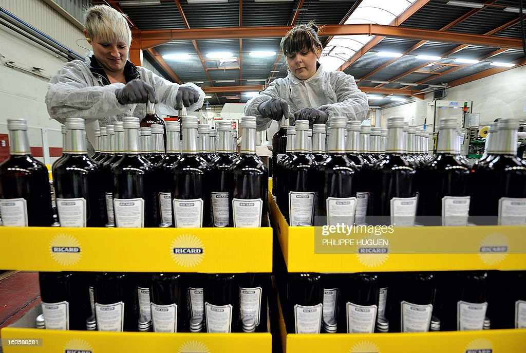 French spirit Pernod-Ricard employees work on the chain of bottling of star aniseed-based spirit Ricard on January 31, 2013 in Vendeville, northern France. The famous star anise spirit Ricard was created in 1932 by French Paul Ricard and became Pernod-Ricard group in 1975. AFP PHOTO PHILIPPE HUGUEN