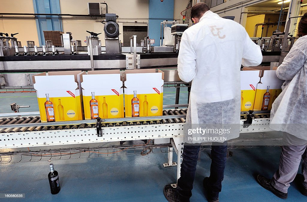 French spirit Pernod-Ricard employees work on the chain of packaging of star aniseed-based spirit Ricard on January 31, 2013 in Vendeville, northern France. The famous star anise spirit Ricard was created in 1932 by French Paul Ricard and became Pernod-Ricard group in 1975.