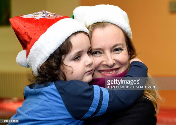 French sponsor of the movement 'Copains du monde' Valerie Trierweiler hugs a child during a visit on December 20 2016 in Nilvange eastern France...