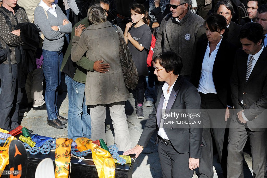 French Sports Minister Valerie Fourneyron puts her hand on the coffin of one of the French mountain guides Ludovic Challeat and Fabrice Priez, as people comfort each other, during a memorial ceremony to pay tribute to the victims of the last week avalanche on Nepal's Manaslu mountain, on October 2, 2012, in Chamonix, that is considered the birthplace of European alpinism and the home of most of the French climbers killed. The four French -- two guides and two clients -- were among eight people killed after an avalanche swept through their camp on the side of the 8,156-metre (26,759-foot) Himalayan mountain, just hours before the alpinists were to make an attempt to reach the peak's summit.