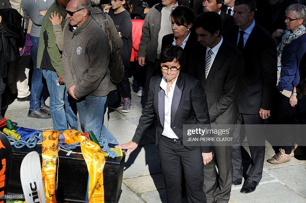 French Sports Minister Valerie Fourneyron puts her hand on the coffin of one of the French mountain guides Ludovic Challeat and Fabrice Priez, during a memorial ceremony to pay tribute to the victims of the last week avalanche on Nepal's Manaslu mountain, on October 2, 2012, in Chamonix, that is considered the birthplace of European alpinism and the home of most of the French climbers killed. The four French -- two guides and two clients -- were among eight people killed after an avalanche swept through their camp on the side of the 8,156-metre (26,759-foot) Himalayan mountain, just hours before the alpinists were to make an attempt to reach the peak's summit. AFP PHOTO / JEAN-PIERRE CLATOT