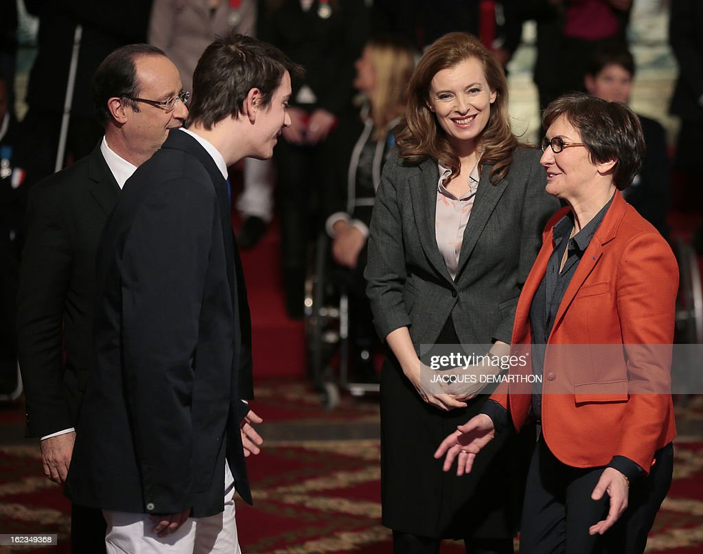 French Sports Minister Valerie Fourneyron (R) speaks to French athlete Pascal Pereira-Leal, table tennis bronzer medalist in the 2012 London Paralympic Games, as French President Francois Hollande (L) and his companion Valerie Trierweiler (2ndR) look on after the champion was awarded Knight in the Order of Merit, during an awarding ceremony at the Elysee presidential Palace on February 22, 2013 in Paris. AFP PHOTO / POOL / JACQUES DEMARTHON
