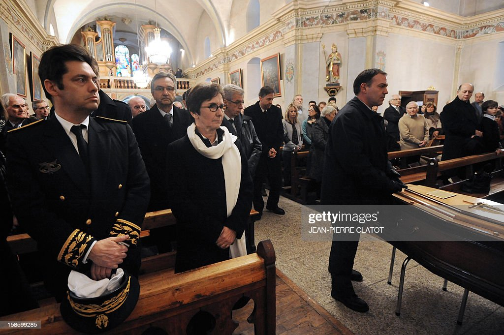French Sports minister Valerie Fourneyron (3rdL) stands near th the coffin of French climber Maurice Herzog during his funeral ceremony, on December 20, 2012 at the Saint-Michel church in Chamonix, French Alps. Maurice Herzog, the French climber who conquered Annapurna in the first recorded ascent of a peak above 8,000 metres, has died at the age of 93, on December 13.
