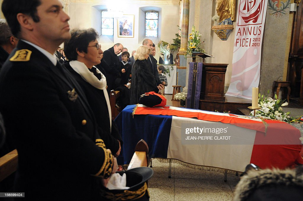 French Sports minister Valerie Fourneyron (2ndL) stands near the coffin of French climber Maurice Herzog during his funeral ceremony, on December 20, 2012 at the Saint-Michel church in Chamonix, French Alps. Maurice Herzog, the French climber who conquered Annapurna in the first recorded ascent of a peak above 8,000 metres, has died at the age of 93, on December 13.