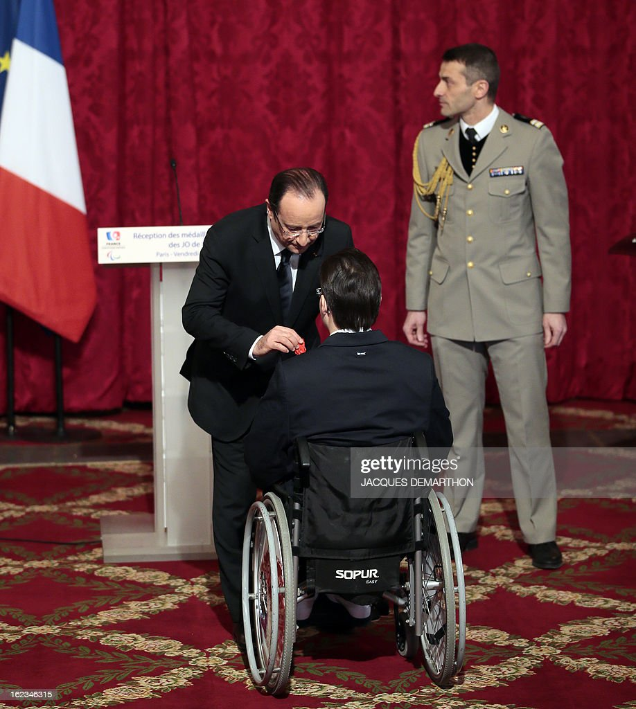 French sports-shooter and 2012 London Paralympic Games gold medalist Cedric Fevre-Chevalier receives the Legion of Honor decoration from France's President Francois Hollande (L) during an awards ceremony at the Elysee Palace on February 22, 2013 in Paris.
