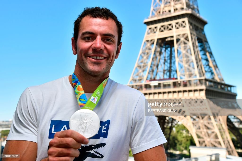 French sprint canoeist Maxime Beaumont poses with his silver medal on August 23 in front of the Eiffel tower in Paris France's Olympic team landed in...