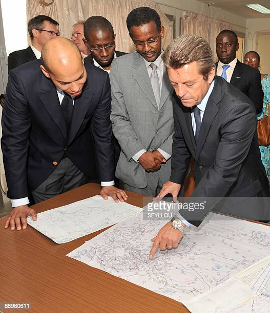 French State Secretary for Cooperation Alain Joyandet points at a map with technician Youssouf Mohamat as he visits with Senegalese Transport...