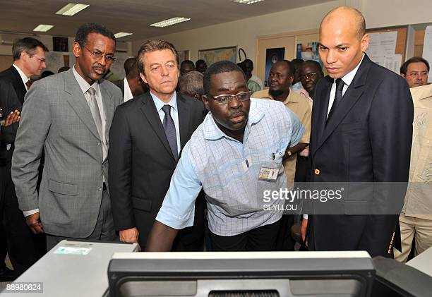 French State Secretary for Cooperation Alain Joyandet visits with technician Youssouf Mohamat and Senegalese Transport Minister Karim Wade on July 11...