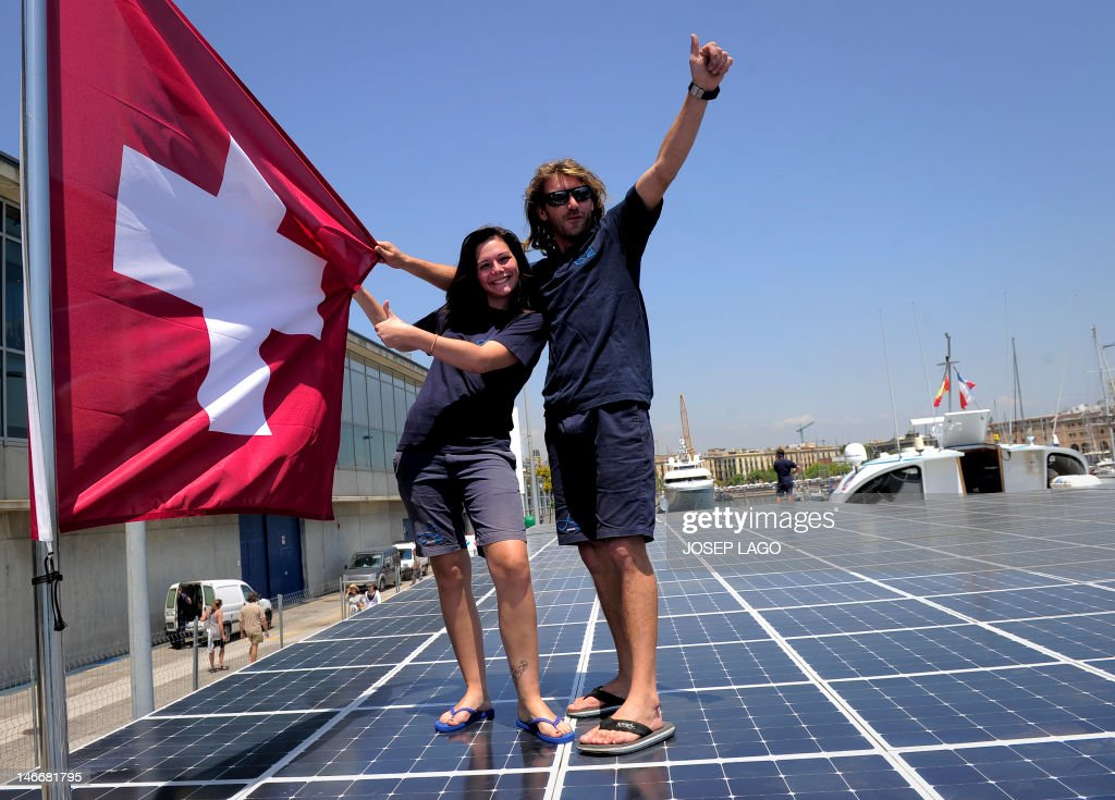 French Stewardess Nikita Dumont-Ray (L) and French first Mate Thomas David (R) pose with a Swiss flag on the deck of The PlanetSolar boat, the first solar-powered boat to travel around the world, as it is docked at Barcelona's harbour on June 22, 2012. The 31m by 15m white catamaran was unveiled to the world in 2010 and will embark on a Meditarranean tour this summer to promote solar energy for pollution-free shipping. The Swiss-flagged boat, which was built in Germany, is topped by 500 square metres of black solar panels, with a bright white cockpit sticking up in the centre.
