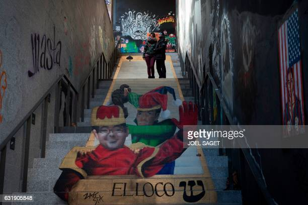 French street art duo Zag and Sia pose in front of one of their works on a stairway in Paris on January 17 2017 The work features a portrait of...