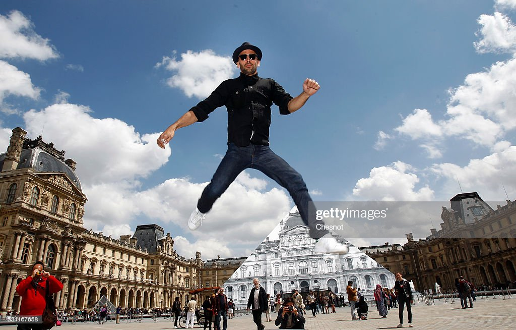 French street artist and photographer JR jumps in front of the Louvre museum on May 25, 2016 in Paris France. French street artist JR has installed a huge photographic collage on the Louvre pyramid for making it disappear and creating a giant optical illusion through an anamorphosis, a technique that allows to appear or disappear a work.