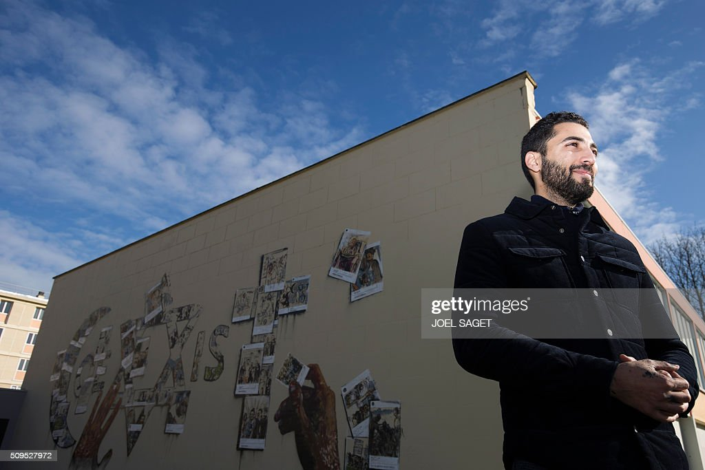 French street artist Combo attends the inauguration of his fresco '#CoexistSarcelles' on February 11, 2016 in Sarcelles, northern suburb of Paris. / AFP / JOEL SAGET