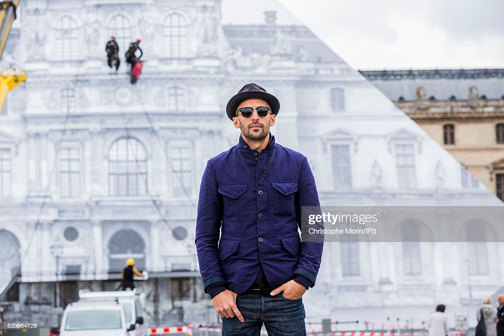 French street artist JR poses for a photo outside The Louvre on May 24, 2016 in Paris, France. The artist has covered The Louvre Pyramid by an optical illusion made with black and white photos of 16th century buildings and is open to the public from May 25 to June 27, 2016.