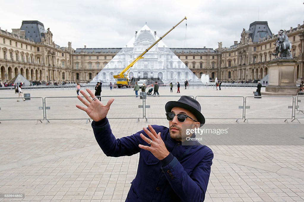 French street artist JR poses in front of the Louvre museum on May 24, 2016 in Paris France. French street artist JR has installed a huge photographic collage on the Louvre pyramid, for making it disappear and creating a giant optical illusion through an anamorphosis, a technique that allows to appear or disappear a work.