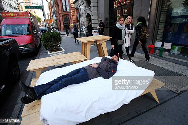 French street artist Sebastien Renauld lays on a bed along a footpath on Broadway in New York on October 20 2015 Renauld and Laurent Boijeot the two...