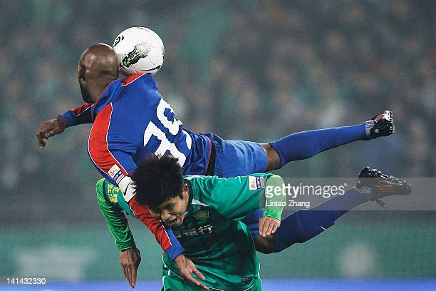 French striker Nicolas Anelka of Shanghai Shenhua clashes with opponent Yu Yang of Beijing Guoan during the Chinese Super League match at Workers...