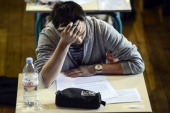 A French student works on the test of philosophy as he takes the baccalaureat exam on June 16 2014 at the Jacques Decour high school in Paris AFP...
