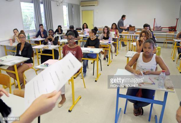 French students work on the test of philosophy as they take the baccalaureat exam on June 16 2014 at the Moulin Joli high school in La Possession on...