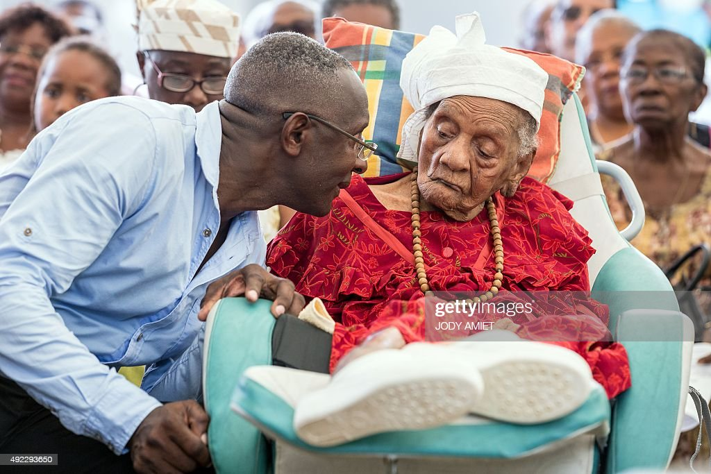 French supercentenarian and France's oldest living person in France Eudoxie Baboul 114 year listens to her grandson Joubert Baboul during a mass...