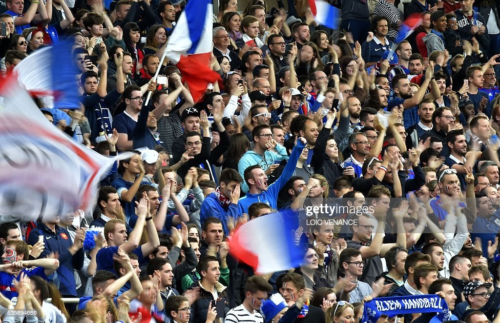 French supporters hold the French National flag as they attend the International friendly football match between France and Cameroon at the Beaujoire stadium, in Nantes, western France, on May 30, 2016 as part of the French team's preparation for the upcoming Euro 2016 European football championships. / AFP / LOIC