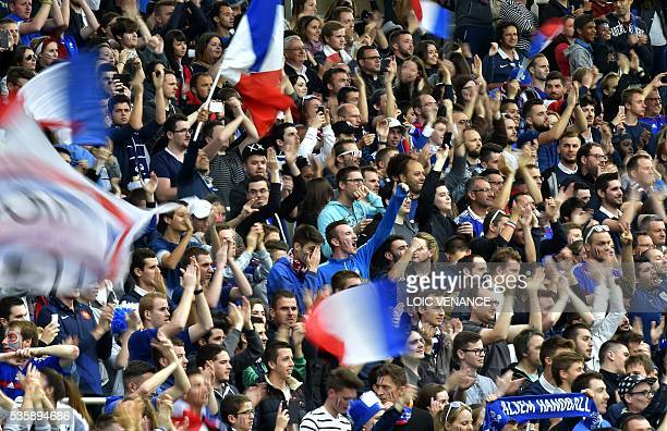 French supporters hold the French National flag as they attend the International friendly football match between France and Cameroon at the Beaujoire...