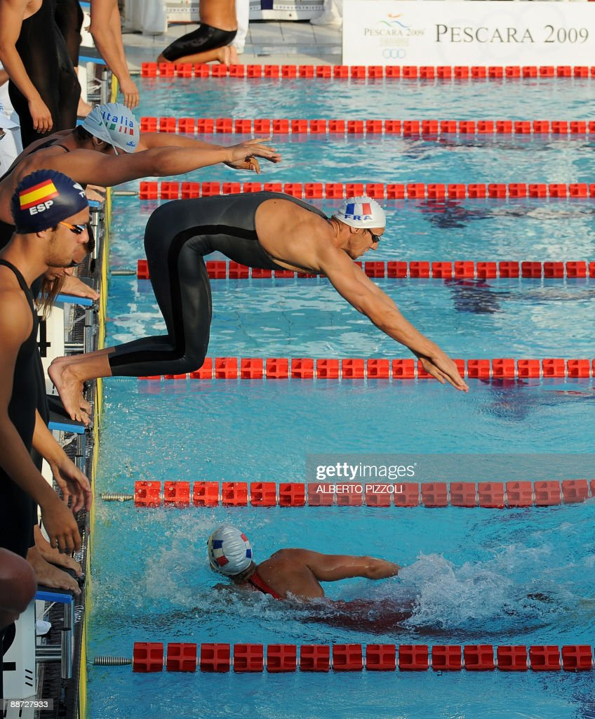 French swimmer Alain Bernard dives during Men's 4x400m Freestyle final with teammates Amaury Leveau, Fredric Bousquet and William Meynard at the XVI Mediterranean Games in Pescara on June 28, 2009. France won .