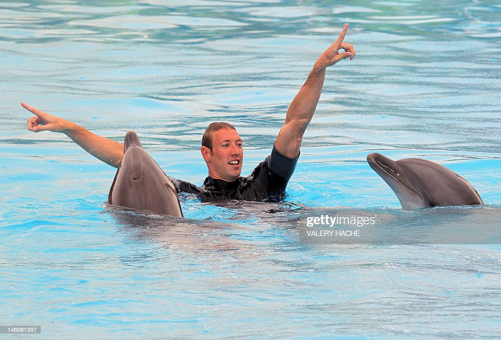 French swimmer Alain Bernard gestures as he swims with dolphins at Marineland, an animal exhibition park, on June 20, 2012 in Antibes, southern France. Alain Bernard is qualified for the 2012 Summer Olympic Games in London next July.