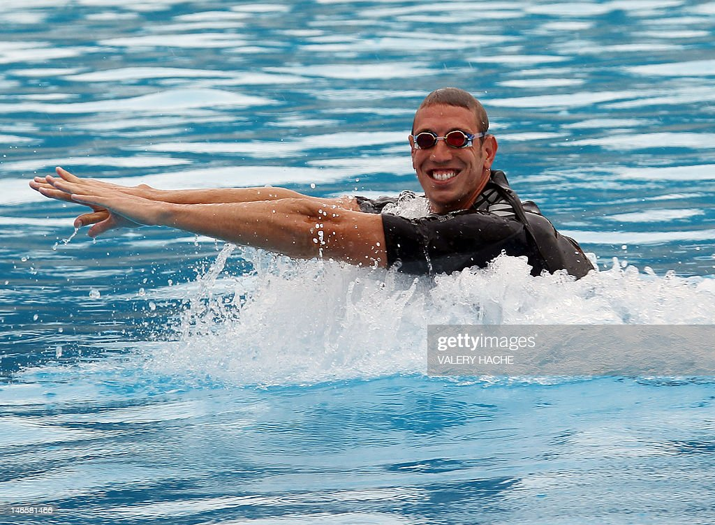 French swimmer Alain Bernard moves on the back of a dolphin at Marineland, an animal exhibition park, on June 20, 2012 in Antibes, southern France. Alain Bernard is qualified for the 2012 Summer Olympic Games in London next July.