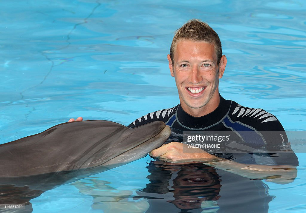 French swimmer Alain Bernard poses after swiming with dolphins at Marineland, an animal exhibition park, on June 20, 2012 in Antibes, southern France. Alain Bernard is qualified for the 2012 Summer Olympic Games in London next July. AFP PHOTO / VALERY HACHE