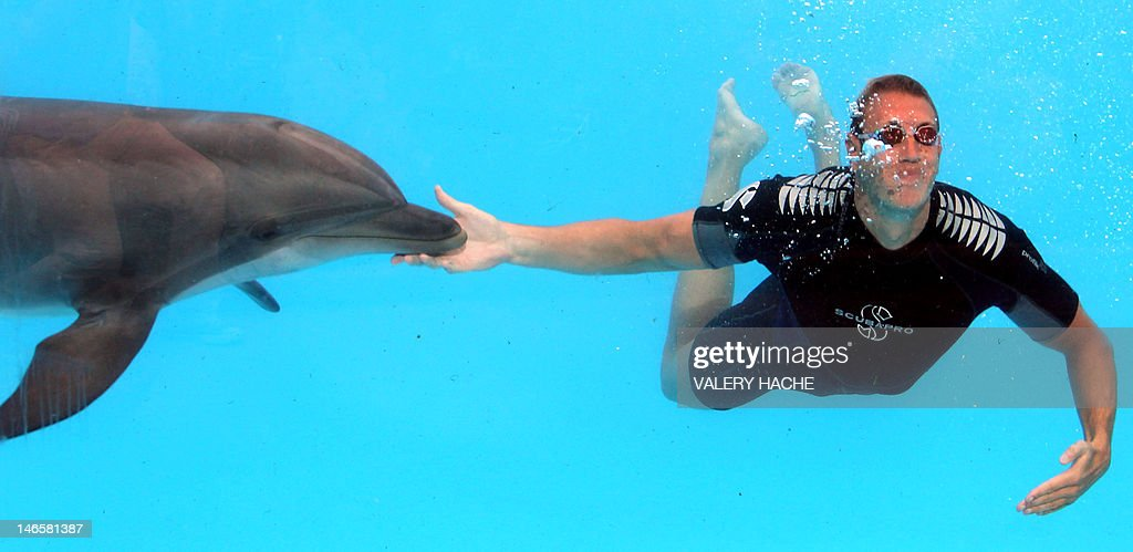 French swimmer Alain Bernard swims with a dolphin at Marineland, an animal exhibition park, on June 20, 2012 in Antibes, southern France. Alain Bernard is qualified for the 2012 Summer Olympic Games in London next July. AFP PHOTO / VALERY HACHE