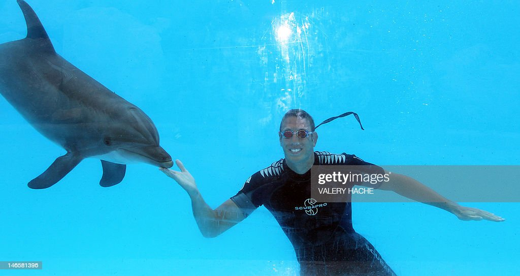 French swimmer Alain Bernard swims with a dolphin at Marineland, an animal exhibition park, on June 20, 2012 in Antibes, southern France. Alain Bernard is qualified for the 2012 Summer Olympic Games in London next July.