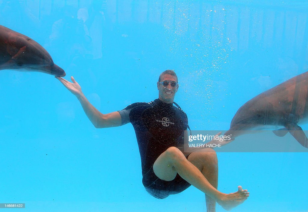 French swimmer Alain Bernard swims with dolphins at Marineland, an animal exhibition park, on June 20, 2012 in Antibes, southern France. Alain Bernard is qualified for the 2012 Summer Olympic Games in London next July.