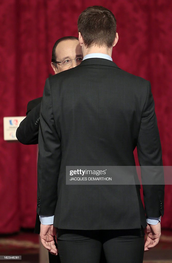 French swimmer and 2012 London Paralympic Games gold medalist Charles Rozoy receives the Legion of Honor decoration from France's President Francois Hollande (L) during an awards ceremony at the Elysee Palace on February 22, 2013 in Paris.