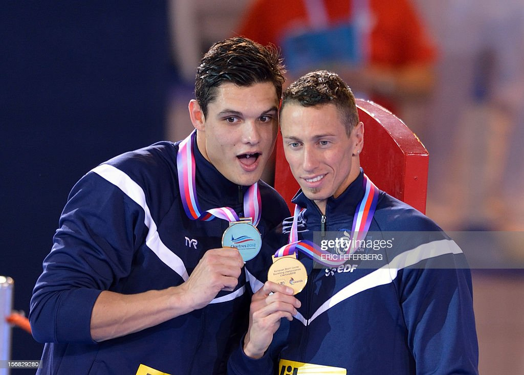 French swimmer Florent Manaudou (L) celebrates on the podium with his gold medal beside French swimmer and bronze medalist Frederick Bousquet after the men's 50m freestyle at the European Swimming Championships on November 22, 2012, in Chartres.